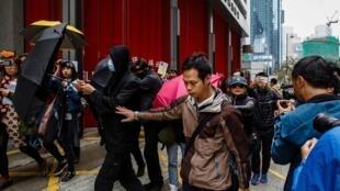 Những người tới dự phiên tòa để ủng hộ ba thanh niên Hồng Kông biểu tình phản đối Bắc Kinh, khi rời tòa án đã dùng ô che mặt, ngày 17/03/2017.