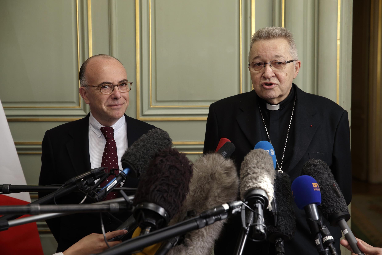 El ministro francés del interior, Bernard Cazeneuve (izquierda) y el arzobispo de París, Cardenal André Vingt-Trois, hablan a la prensa el 23 de abril de 2015, luego del descubrimiento de los planes del terrorista Sid Ahmed Ghlam contra dos iglesias.
