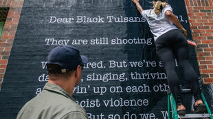 La artista Tatyana Fazlalizadeh cuelga un cartel en el distrito de Greenwood de Tulsa el 28 de mayo de 2021 en Tulsa, Oklahoma, antes de la conmemoración del centenario de la masacre racial de Tulsa