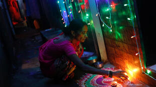 A woman decorates her house on the eve of Diwali Hindu festival in a slum in Mumbai, India