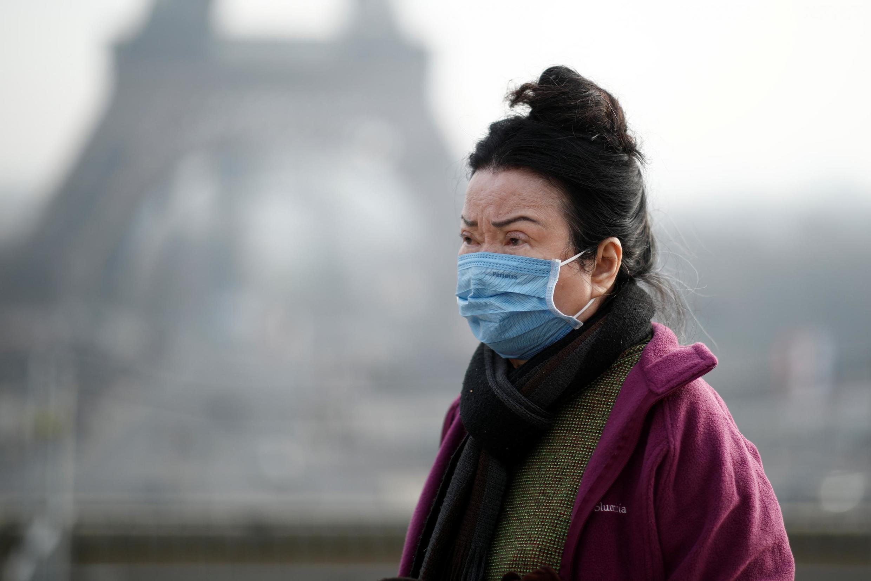 Mulher porta máscara em Trocadero, em frente à Torre Eiffel, em Paris. Em 25 de janeiro de 2020.