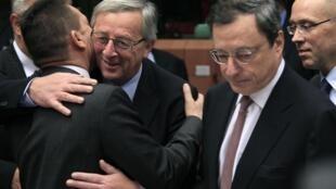O presidente do Eurogroupo, Jean-Claude Juncker, cumprimenta o ministro das Finanças grego, Yannis Stournaras, ao lado do presidente do BCE, Mario Draghi, no dia 12 de novembro de  2012, em Bruxelas.