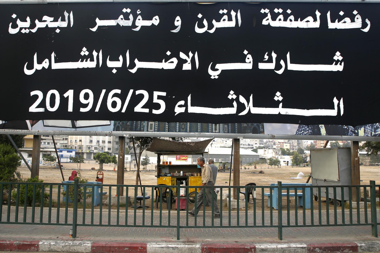 """Cartaz em Gaza denunciando a conferência de Bahrein: """"Para rejeitar o """"acordo do século"""" da conferência no Bahrein, junte-se à greve geral nesta terça-feira 25/6/2019."""
