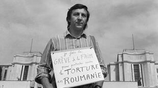 """Virgil Tanase, the Romanian-born, naturalized French dissident writer, holding a pancart which reads: """"I'm doing a hunger strike against torture in Romania"""" on 23 July 1982 in Paris."""