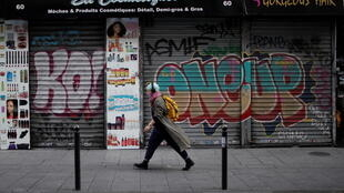 A woman, wearing a protective face mask, walks past a closed hair and cosmetic shop in a street in Paris during the second nationwide lockdown.