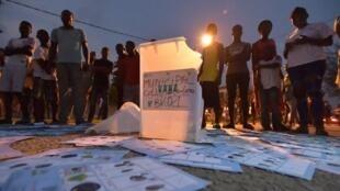 Des habitants de Grand-Bassam autour d'une urne et de bulletins saccagés dans les rues de la ville, le 16 décembre 2018.