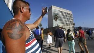 Un cubano tatuado con las banderas cubanas y estadounidenses toma una foto de la sección de intereses de Estados Unidos en La Habana.
