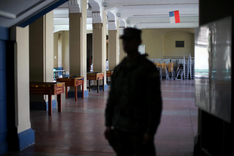 Silhouette d'un militaire chilien à l'intérieure d'une école réquisitionnée comme bureau de vote pour les élections municipales du 23 octobre 2016.