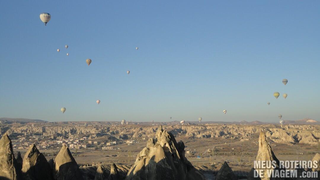 Foto da região da Capadócia sobrevoada por balões com turistas.