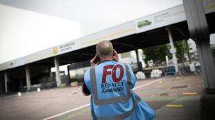 Un représentant syndical de FO se tient devant l'usine de Sandouville de Renault, le 22 mai 2020, à sa réouverture après les mesures de confinement dues au coronavirus