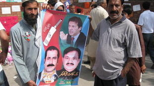 Two supporters brandish a PTI poster outside the Shaukat Hanum hospital