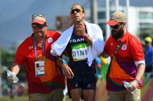 Le marcheur français Yohann Diniz (c) soutenu par deux officiels après le 50 km aux JO de Rio, le 19 août 2016.
