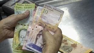 Un cajero cuenta billetes de bolívares venezolanos.