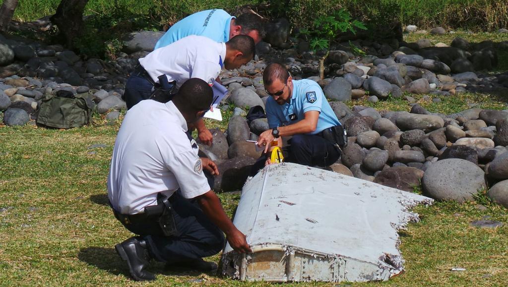 Askari polisi wa Ufaransa wakikagua kipande cha bawa la ndege kiliyopatikana kwenye pwani ya kisiwa cha Réunion, Juni 29, 2015.