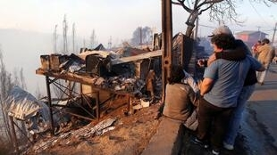 Des gens à côté des débris de leur maison après la propagation des incendies de forêt à Valparaiso, au Chili, le 24 décembre 2019.