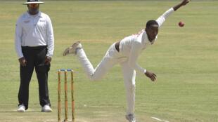 Umpire Nitin Menon keeps watch as Zimbabwe's Tinotenda Mutombodzi bowls against Sri Lanka in January 2020