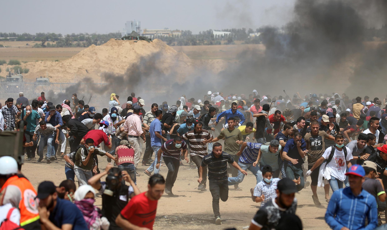 (Ảnh minh họa) - Người Palestine bỏ chạy sau khi quân đội Israel pháo kích khu vực biên giới giữa dải Gaza và Israël, vào « Ngày Jérusalem » 08/06/2018.
