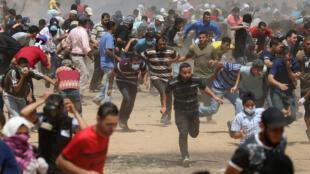Des Palestiniens fuient les tirs des militaires israéliens près de la frontière entre Gaza et Israël, lors de la mobilisation à l'occasion de la «Journée de Jérusalem», à Gaza, le 8 juin 2018.