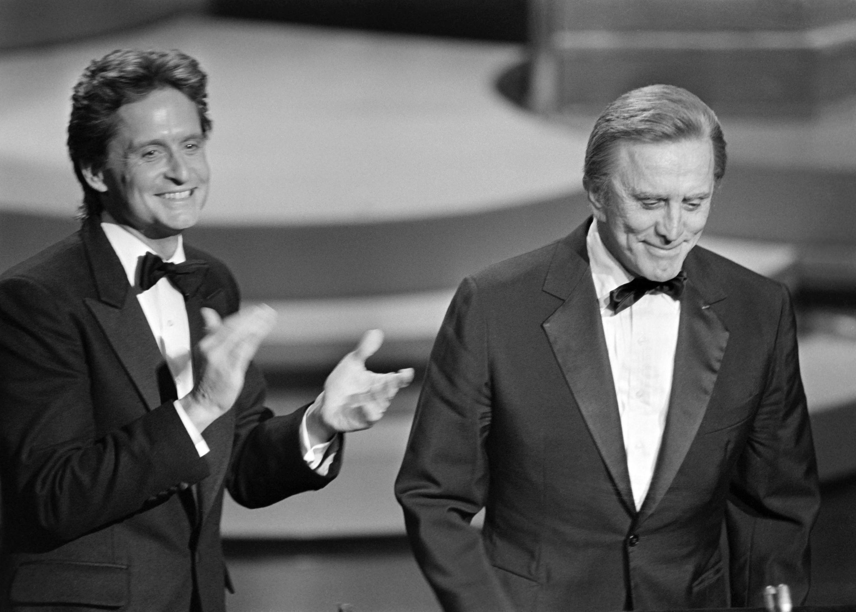 Le 25 mars 1985, l'acteur américain Michael Douglas (L) applaudit son père, Kirk Douglas, lors de la 57e cérémonie des Oscars, à Hollywood, en Californie.