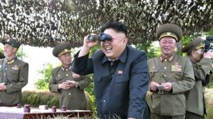 Hoton shugaban Korea ta Arewa  Kim Jong Un na hangen nesa da naurori yayin da yake kallon wani atasaye na soja.