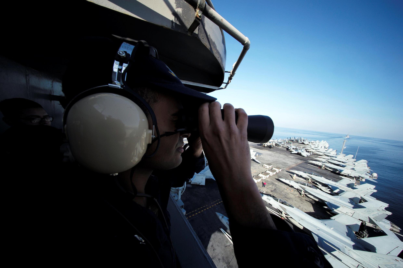 Un soldat américain surveille le pont du porte-avions USS John C. Stennis alors qu'il passe le détroit d'Ormuz, lieu de tensions géopolitiques.