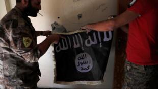 Des membres des Forces démocratiques syriennes s'emparent d'un drapeau jihadiste de l'EI, à Raqqa, le 4 octobre 2017.