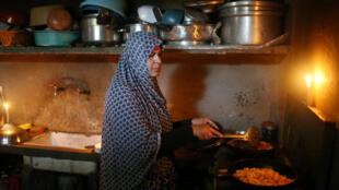 Sem energia elétrica, mulher prepara comida à luz de velas em Gaza em 12 de junho de 2017