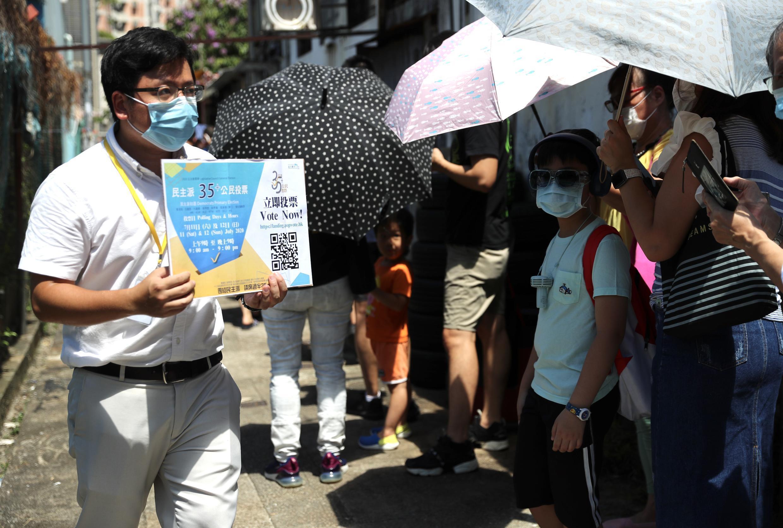 Un voluntario muestra un panel con información a la gente que está esperando para votar en las elecciones primarias de los partidos prodemocracia en Hong Kong, el 11 de julio de 2020