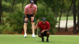 Tiger Woods and retired NFL player Peyton Manning read a putt on the sixth green during a four-man charity golf tournament at Medalist Golf Club in Florida which serves as Woods' home golf course.