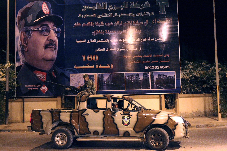 Des membres des forces spéciales libyennes, fidèles au maréchal Haftar passent devant une grande affiche dédiée à Khalifa Haftar, à Benghazi, le 19 septembre 2017.