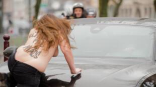 """2015年2月10日法國里爾法庭審理""""卡爾頓酒店淫媒案"""",女權主義者爬上卡恩乘坐汽車抗議。"""