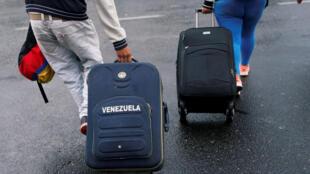 Des migrants vénézuéliens font rouler leurs valises sur le Pont Rumichaca, à la frontière de la Colombie et de l'Equateur, le 18 août 2018.