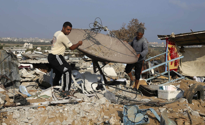Palestinos aproveitam a trégua em Gaza para resgatar objetos em meio a destroços.