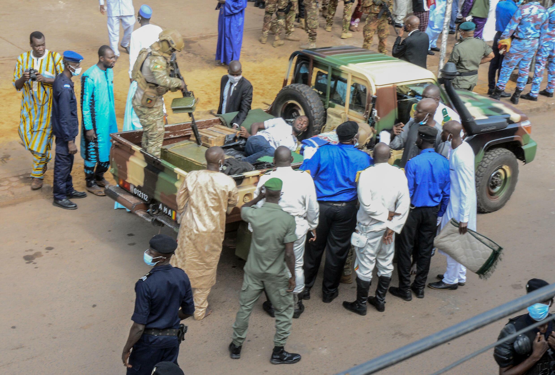 El personal de seguridad observa a un presunto atacante (C) mientras yace en la parte trasera de un vehículo frente a la Gran Mezquita Fayçal en Bamako, Malí, el 20 de julio de 2021, tras un intento de atentado contra el presidente Assimi Goita