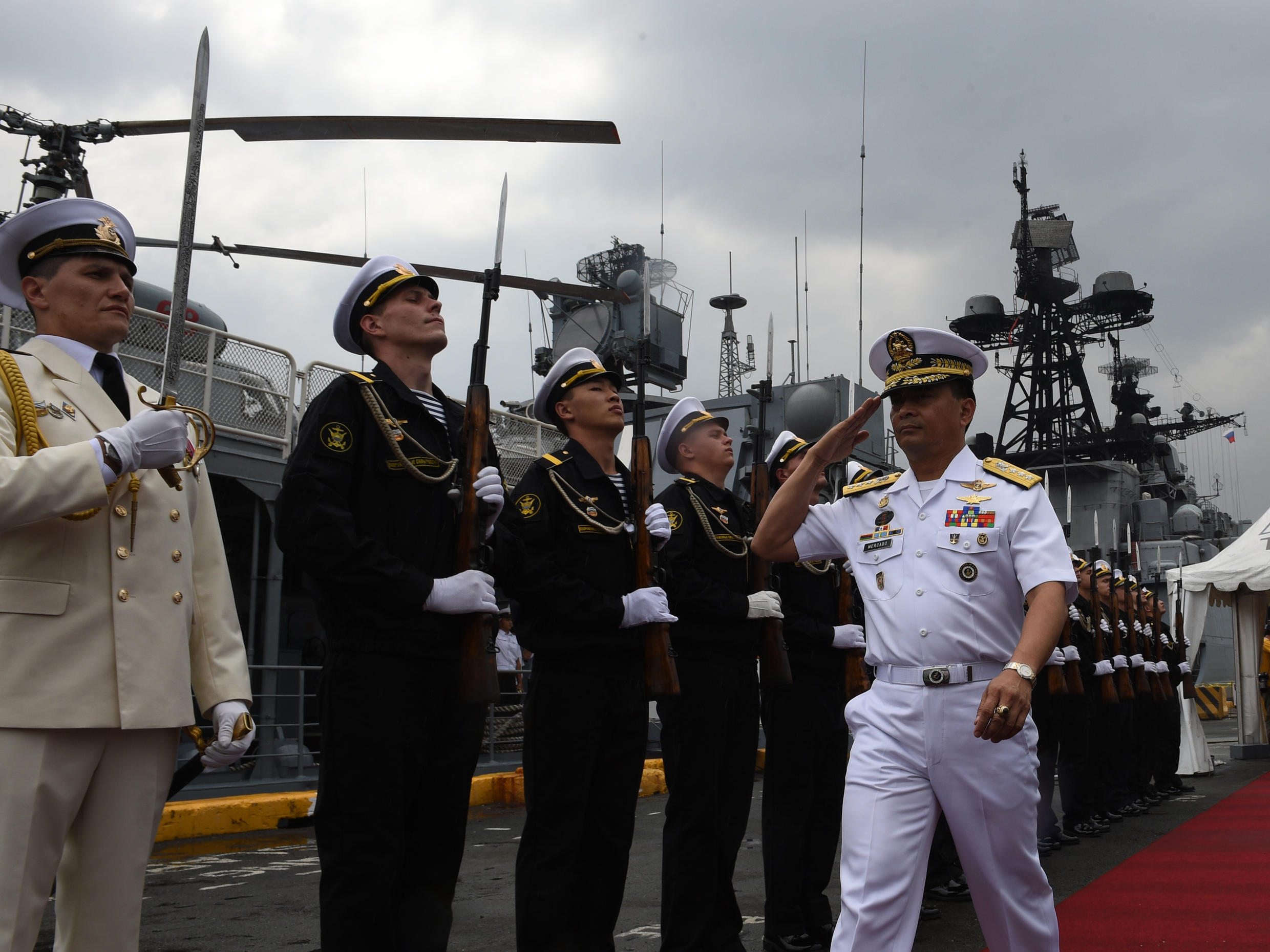 This file photo taken on January 5, 2017 shows Philippine Navy Chief Vice Admiral Ronald Joseph Mercado (R) saluting while reviewing Russian sailors after visiting the Russian anti-submarine ship Admiral Tributs at the south pier in Manila.