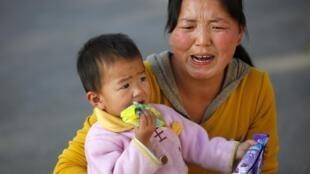 Un taux anormalement élevé de plomb a été décelé chez les enfants de la province de Henan, dont cet enfant, âgé de un an, dans les bras de sa mère, le 15 octobre 2009.