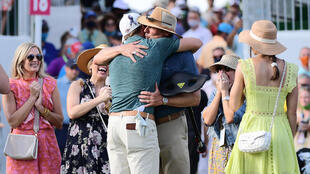 Sam Burns, his back to the camera, hugs his father as he celebrates with his family on the 18th green after winning his first US PGA title at the Valspar Championship