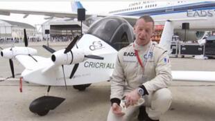 Didier Esteyne, pilote du Cri Cri, pose à côté de l'avion électrique hyper léger au Salon de l'aéronautique du Bourget en 2011.
