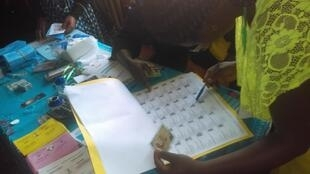 A voter checks her name on Cameroon's electoral list in Sunday's parliamentary and municipal elections, 09 February 2020