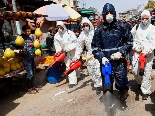Wasu jami'an lafiya yayin aikin tsaftace babbar kasuwar yankin Gaza don dakile yaduwar annobar murar coronavirus.