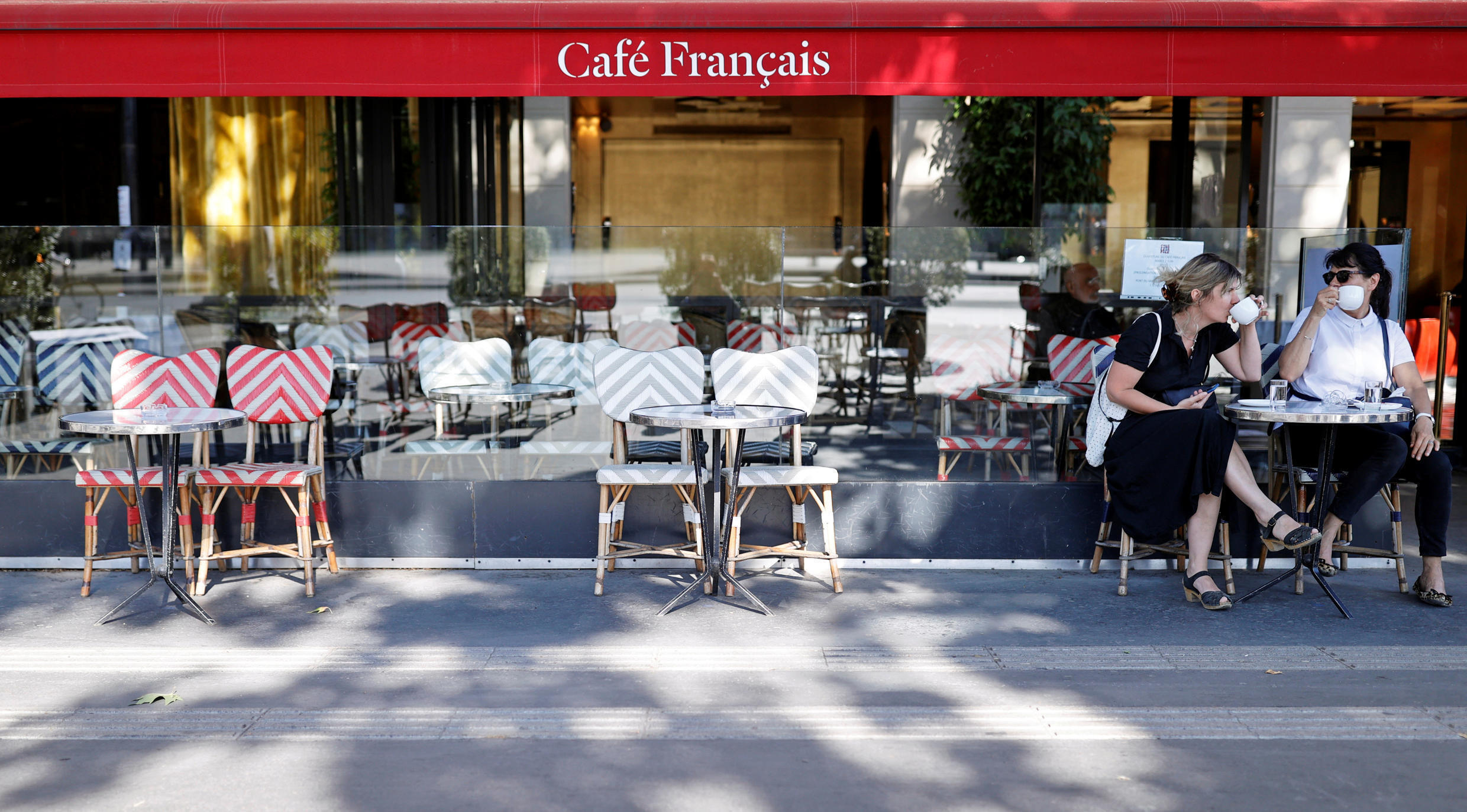 Women sit in Café Français near Bastille, as restaurants and cafes reopen following the coronavirus outbreak, Paris on 2 June, 2020.