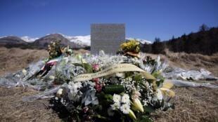 Les fleurs s'amoncellent au pied de la stèle érigée près du village du Vernet en hommage aux victimes du crash de l'Airbus de la Germanwings mardi 24 mars 2015.