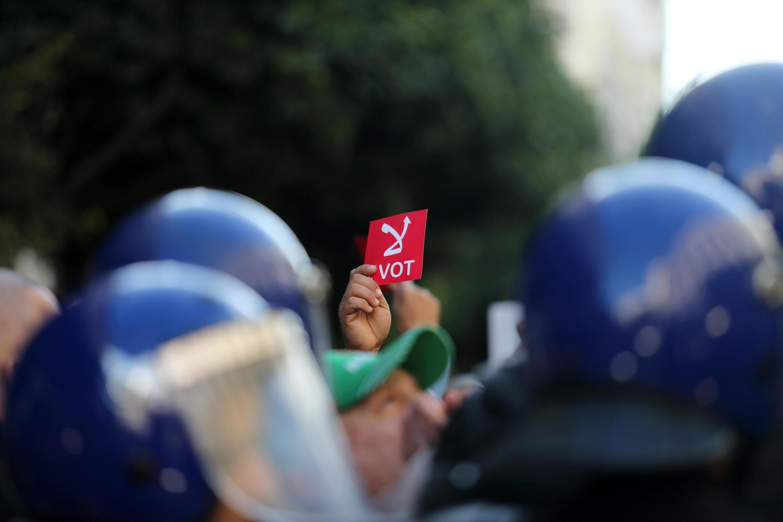 Un manifestant brandit un carton rouge «Je ne vote pas» lors d'une mobilisation à Alger, la veille de l'élection présidentielle contestée, le 11 décembre.