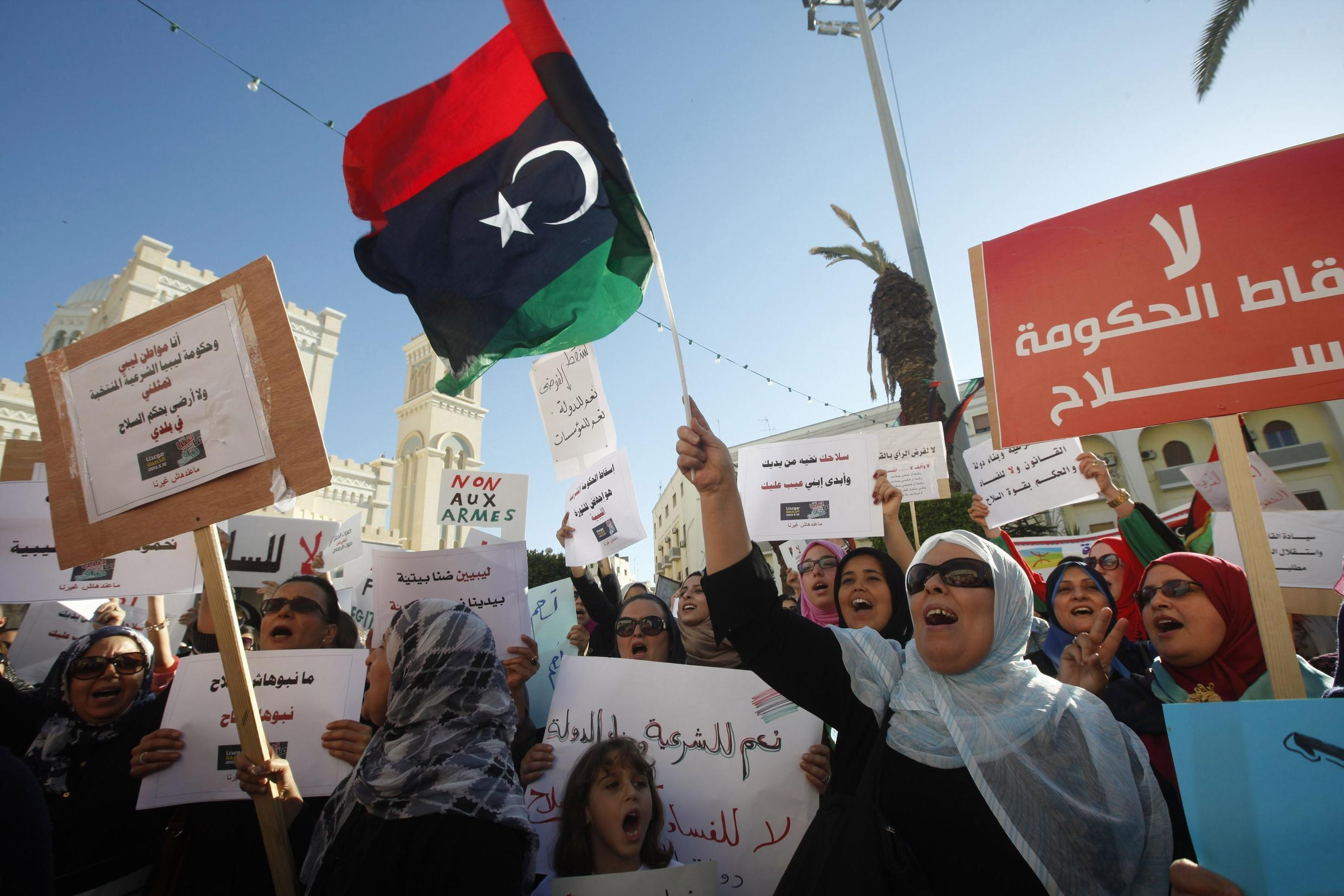 Pro-government protesters with signs and the Libyan flag rally against the use of violence, after gunmen seized control of two government ministries, in Algeria Square in Tripoli.