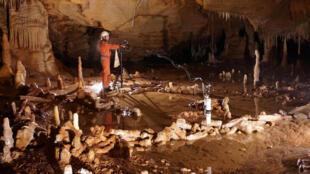 Un scientifique prend des mesures dans la grotte de Bruniquel, située dans le sud-est de la France, où ont été découvertes des constructions en stalagmites datées d'environ 176 500 ans.