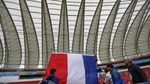 Рабочие поднимают флаг Франции перед матчем Франция-Гондурас на стадионе Бейра-Рио в Порту-Алегре, Бразилия, 15 июня 2014 г.