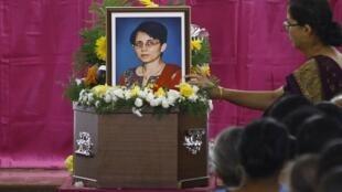 Mulher coloca flores sobre o caixão de Jacintha Saldanha durante a cerimônia religiosa na cidade de Shirva.