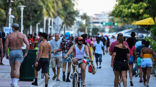 A man rides a bicycle as people walk on Ocean Drive in Miami Beach, Florida on June 26, 2020
