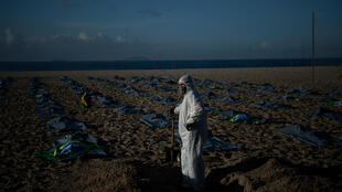 A demonstrator digs a symbolic grave on Copacabana beach, Rio de Janeiro, in front of rows of bags representing Covid deaths during a protest against the Brazilian government's handling of the pandemic