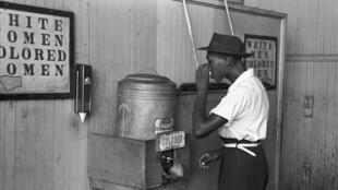 """Cidadão negro americano é constrangido a beber do filtro onde está assinalado """"Apenas para pessoas de cor"""", ou, em inglês, """"Colored only""""."""